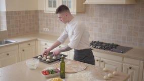 Fabricante joven de la pizza en el uniforme del cocinero que pone las bolas de la pasta para la pizza en la bandeja que cuece en  almacen de metraje de vídeo