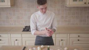 Fabricante joven de la pizza en las bolas rodantes de la pasta del uniforme del cocinero para la pizza en la cocina Concepto de l metrajes