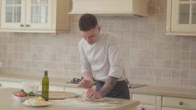 Fabricante joven de la pizza en uniforme del cocinero hábilmente y la pasta kneeding rápida para la pizza en cocina moderna aceit almacen de metraje de vídeo