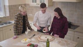 Fabricante joven de la pizza que enseña sus amigos a cómo hacer la pizza en la cocina en casa Pizzaiolo confiado que aplica el to almacen de video