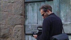 Fabricante video que busca conforme a lanzamiento delante de una puerta vieja SF almacen de metraje de vídeo