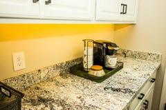 Fabricante y tazas de café en Tray On Kitchen Granite Counter portátil imagenes de archivo