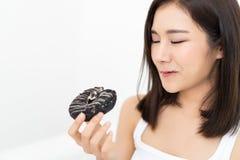 Fabrication asiatique de sourire de butées toriques de chocolat de consommation de femme de plan rapproché jeune photos stock