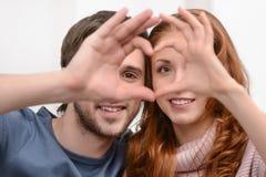 Fabrication d'un coeur. Jeunes couples attrayants faisant un coeur avec le thei Photographie stock libre de droits