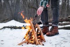 Fabrication d'un feu de camp dans une forêt neigeuse images libres de droits