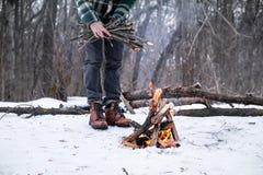 Fabrication d'un feu de camp dans une forêt neigeuse photo libre de droits