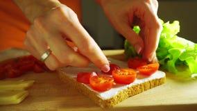 Fabrication d'un sandwich : mise des tomates-cerises sur le pain