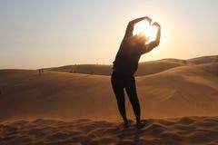 Fabrication d'un symbole d'amour dans le coucher du soleil Image stock