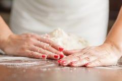 Fabrication de la pâte crue par les mains femelles sur la table images libres de droits