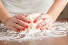 Fabrication de la pâte crue par les mains femelles sur la table image libre de droits