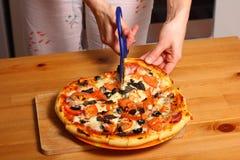 Fabrication de la pizza par les mains femelles sur la table de cuisine Image stock