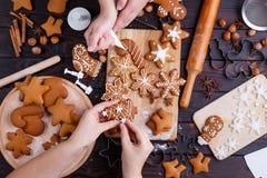 Fabrication de pain d'épice de Noël Amis décorant c fraîchement cuit au four Photo libre de droits