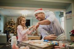 Fabrication des biscuits malpropres de Noël avec le papa Images libres de droits