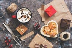 Fabrication des cadeaux pour Noël, papier, ciseaux, fil, chocolat chaud, biscuits sur un fond rustique Le concept des vacances Ch photos stock