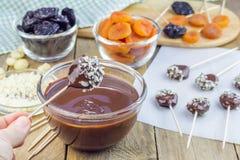 Fabrication des lucettes d'abricot et de pruneaux avec des noisetiers de chocolat et d'Australie Photo stock