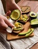 Fabrication des sandwichs avec l'aliment biologique sain d'avocat photo libre de droits