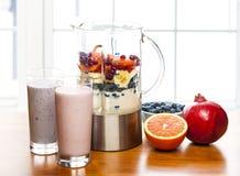 Fabrication des smoothies dans le mélangeur avec le fruit et le yaourt Image stock