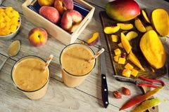 Fabrication des Smoothies de mangue de pêche avec le fruit coupé en tranches Photo stock