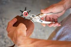 Fabrication des trous avec le perforateur dans l'atelier en cuir photo stock
