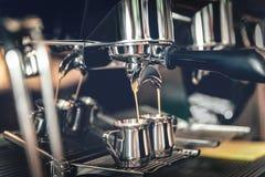 Fabrication du café dans une machine professionnelle de café dans le cafétéria dans les tasses de fer photo stock