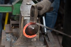 Fabrication du fer à cheval à partir de la tige rouge passionnée images libres de droits