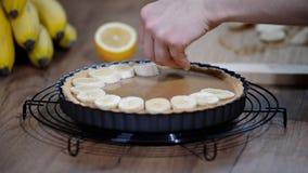 Fabrication du gâteau Banoffi avec le caramel et la banane banque de vidéos