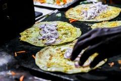 Fabrication du petit pain d'oeufs sur une poêle chaude avec de l'huile et paratha et salade images libres de droits