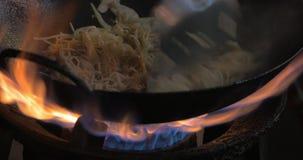 Fabrication du plat de nouilles dans le wok sur le feu de gaz, la Thaïlande banque de vidéos