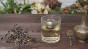 Fabrication du thé sur une table de cuisine foncée banque de vidéos