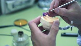 Fabricering av tand- protes, den tand- teknikeren tar bort det överskott vaxet från workpiecen arkivfilmer