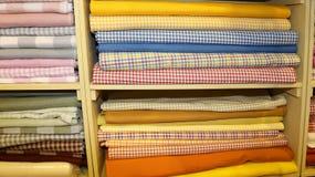 Fabrics of fantasies for sale in the shelf full of haberdashery. Many fabrics of various fantasies for sale in the shelf full stock photography