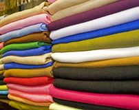 Fabrics on a market stall. Various fabrics stacked on a market stall Stock Images