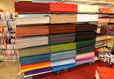 Fabrics for sale at the fair of decoration and leisure time. Shelf full of fabrics for sale at the fair of decoration and leisure time Royalty Free Stock Photo
