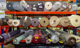 The fabrics on the shelves. Rolls upholstery fabrics stacked on the shelves in the warehouse royalty free stock photo