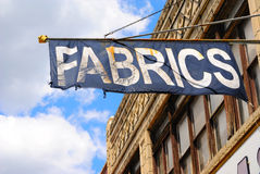 Fabrics Sign. An old flag reading fabrics above a store stock image