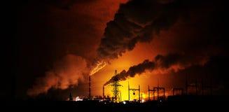 Fabrieken bij nacht, de silhouetten van de pijp die een noxi produceren Stock Afbeelding