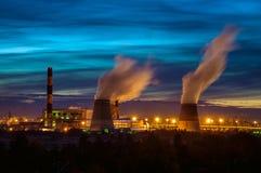 Fabrieken bij nacht, de silhouetten van de pijp die een noxi produceren stock foto