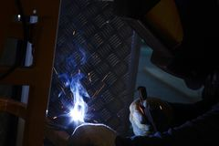 Fabrieksarbeider bij de macro van het fabriekslassen stock afbeelding