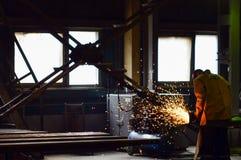 Fabrieksarbeider bij een automobielinstallatie voor de productie van kuilkipwagens en bulldozers, lassend ijzer van een automobie royalty-vrije stock foto's