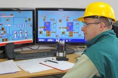 Fabrieksarbeider in controlekamer stock afbeeldingen