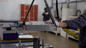 Fabrieksarbeider die een zwaar metaaldeel op kraan vervoeren aan de lijst stock video