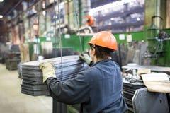 Fabrieksarbeider die lading met kraan vervoeren royalty-vrije stock afbeeldingen