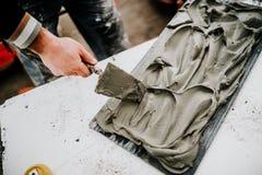 Fabrieksarbeider die op bouwwerf kleefstof op steen en keramische tegels toevoegen royalty-vrije stock afbeeldingen
