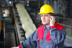 Fabrieksarbeider die op celtelefoon spreekt Stock Foto's