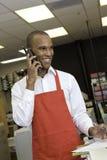 Fabrieksarbeider die op telefoon spreken Stock Foto's