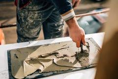 Fabrieksarbeider die troffel en hulpmiddelen om buitenmuren met steen en mortier en kleefstof met behulp van te bouwen stock afbeeldingen