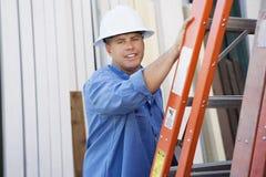 Fabrieksarbeider die zich door een Ladder bevinden royalty-vrije stock foto