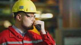 Fabrieksarbeider met walkie-talkie, het controleswerk in een fabriek stock video