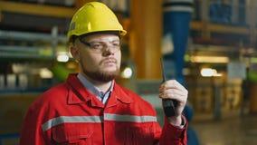 Fabrieksarbeider met walkie-talkie, het controleswerk in een fabriek stock footage