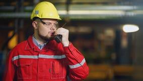 Fabrieksarbeider met walkie-talkie, het controleswerk in een fabriek stock videobeelden